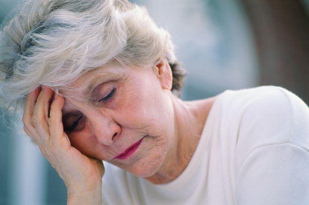 Elderly woman resting her head in her hand